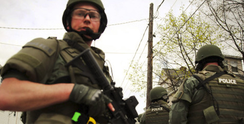 Members of a police SWAT team conduct a door-to-door search for 19-year-old Boston Marathon bombing suspect Dzhokhar A. Tsarnaev on April 19, 2013
